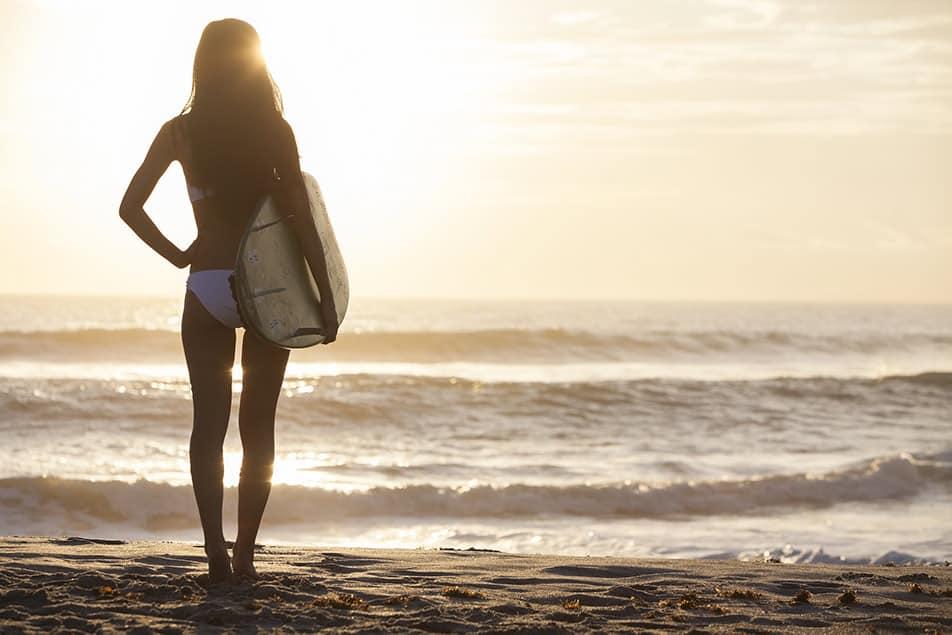 ragazza in riva al mare con tavola da surf