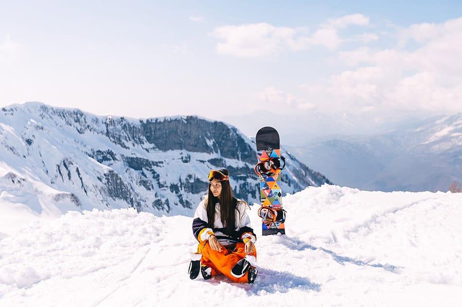ragazza sulla neve con tavola da snowboard